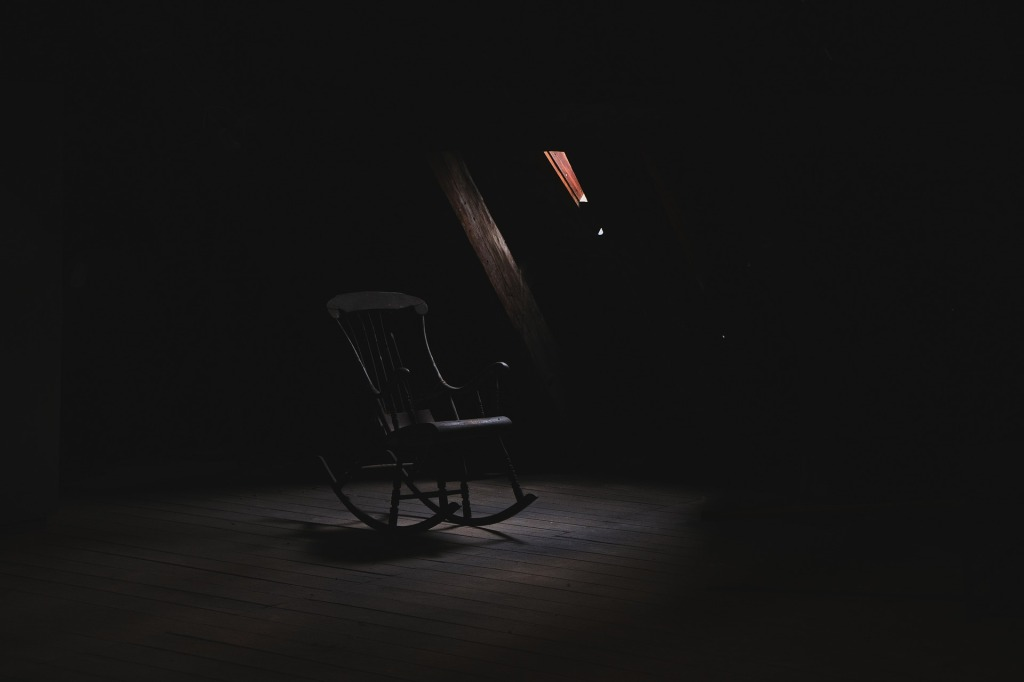 An empty rocking chair in a darkened room